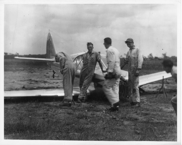 Tony Riccio and four unknown people inspect a damaged Globe Swift airplane sitting on it's wings in a field at Buffalo Airpark.