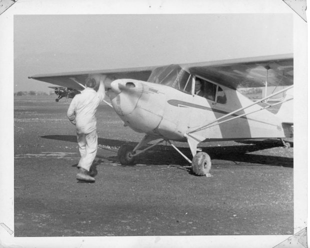 An unknown mechanic hand propping a Piper Cub at Buffalo Airpark.