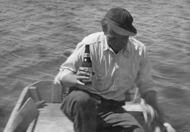 An unknown person sitting in a boat while holding a bottle of beer.