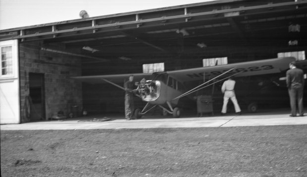 Three unknown people working on an airplane in the Maintenance shop at Buffalo Airpark.