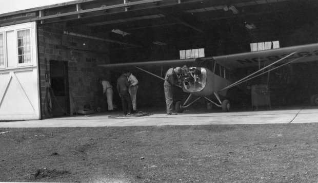Four unknown people working on an airplane in the Maintenance shop at Buffalo Airpark.