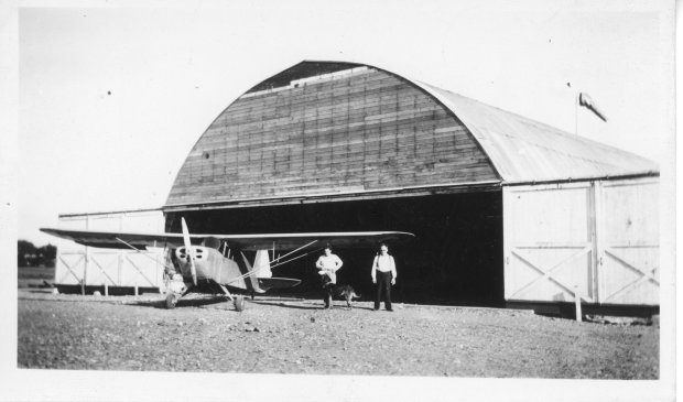 The construction of the Quonset hangar at the Gardenville Airport in August 1944. Tony Riccio, G.B. Baumgarten, and Tony's dog Ivan are standing next to an Interstate S1A F90 airplane.