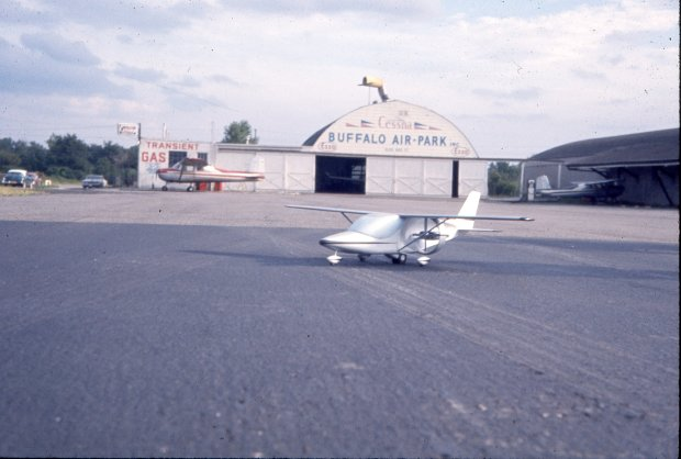 Tony Riccio's model airplane sitting on the tarmac at Buffalo Airpark with the Quonset hangar in the background.