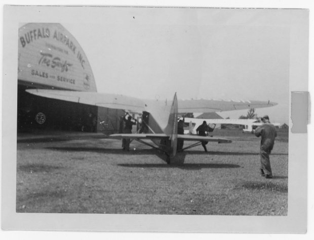 A 1946 Stinson Vultee V-77 is being pushed by three unknown people towards the Quonset hangar at Buffalo Airpark.