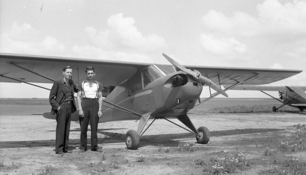 "Tony Riccio and an unknown person standing next to a Taylor ""Cub"" E-2 airplane."