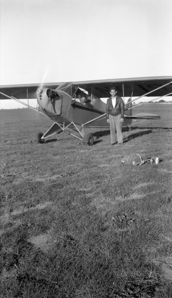 "Tony Riccio standing next to a running Tayler ""Cub"" J-2 with a parachute pack on the ground."