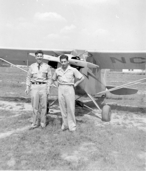 """Tony Riccio and an unknown person standing in front of a Piper J-5 """"Cub""""."""