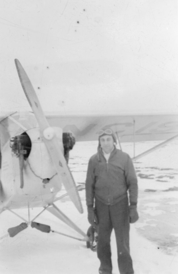 "Tony Riccio standing in front of his J-3 ""Cub"" during the winter season."
