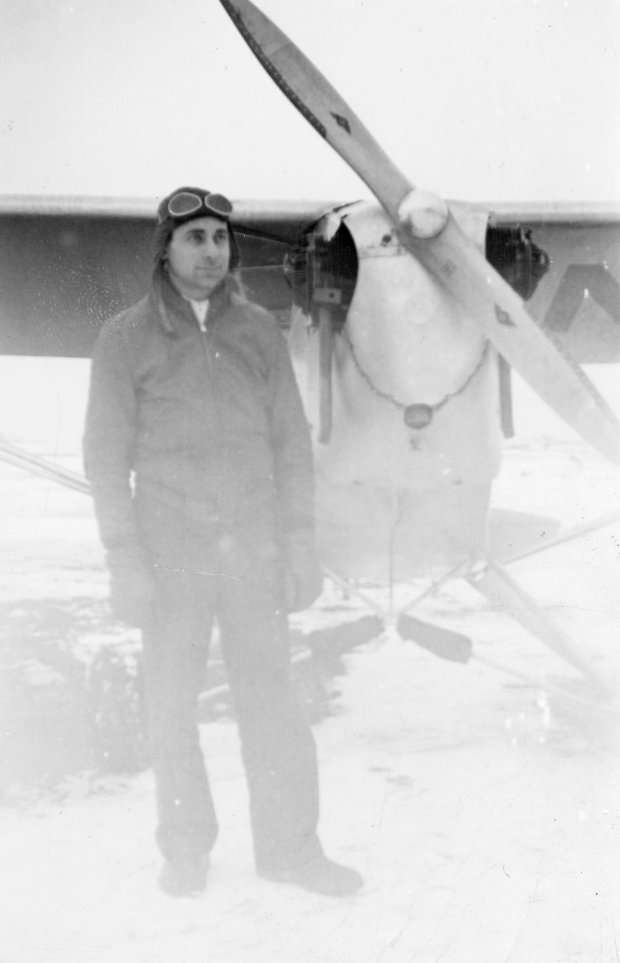 "Tony Riccio standing on the right side of his J-3 ""Cub"" wearing his winter clothing."