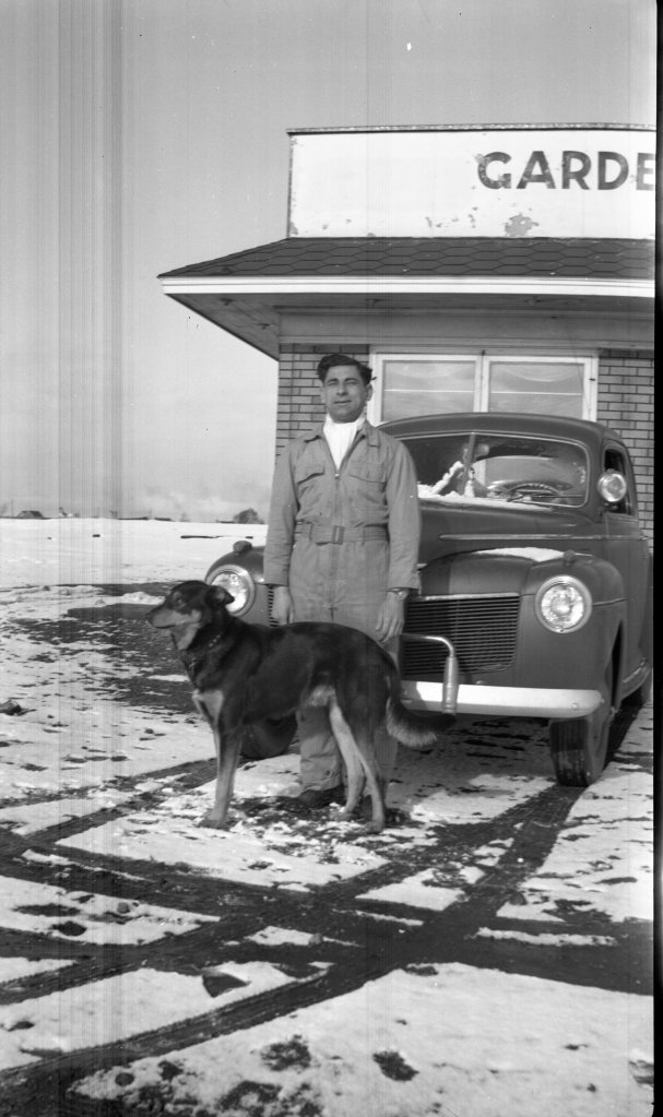 Tony Riccio and his dog Ivan standing in front of the Gardenville Airport operations building during the winter season.