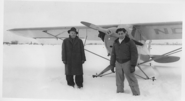 """Tony Riccio and an unknown person standing in front of a Piper J-5 """"Cub"""" with landing skis during the winter season."""