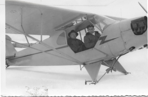 """Tony Riccio and an unknown person sitting in a Piper J-5 """"Cub"""" with landing skis in snow."""