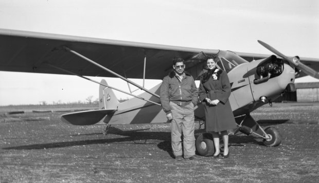 """Tony Riccio and an unknown person standing next to a Piper J-5 """"Cub""""."""