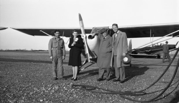"""Tony Riccio and three other unknown people standing in front of a Piper J-4 """"Cub""""."""