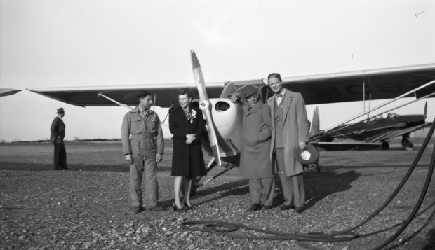 """Tony Riccio and three other unknown people standing in front of a Piper J-4 """"Cub"""". A fifth unknown person is seen in the background."""