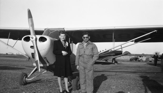 """Tony Riccio and an unknown person standing next to a Piper J-4 """"Cub""""."""