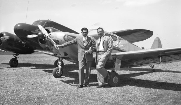 Tony Riccio and an unknown person standing next to a Globe Swift airplane with a Cessna T-50 plane in the background.