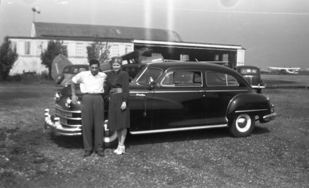 Tony Riccio and his wife Maxine standing in front a car with the Buffalo Airpark's maintenance shop in the background.