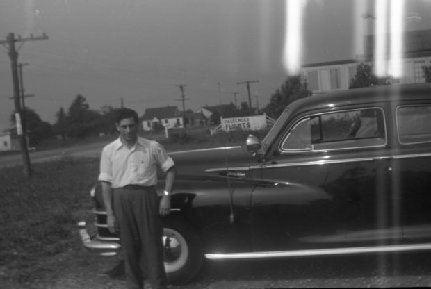 Tony Riccio standing in front of a car in the Buffalo Airpark's parking lot.