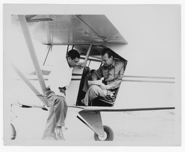 Tony Riccio and an unknown person looking at a map in a Piper Pacer 125 with the door open.