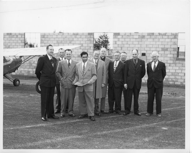 Tony Riccio and nine unknown people grouped together outside of a hangar's brick wall.