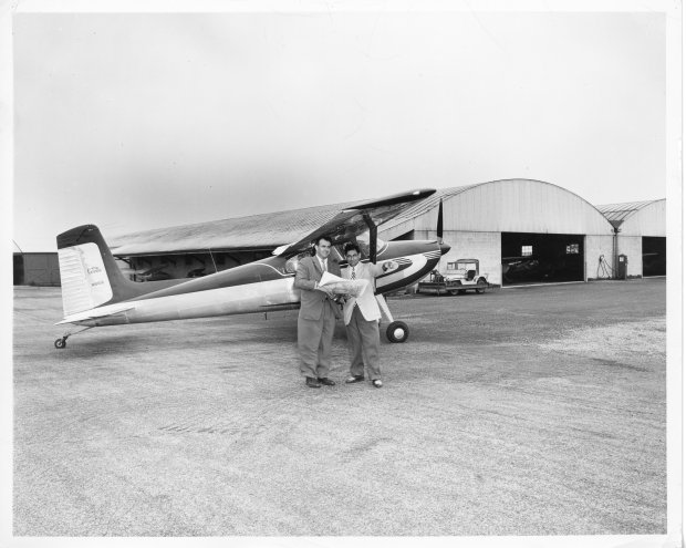 Tony Riccio giving directions to an unknown person standing next to a Cessna 180 with the Buffalo Airpark's twin hangars in the background.