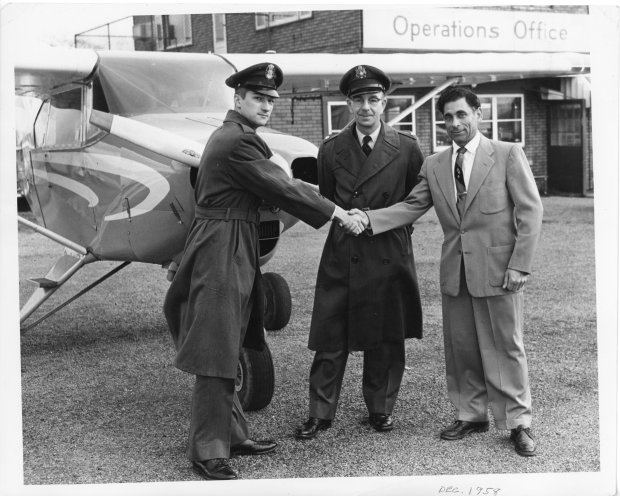 Tony Riccio and two unknown people shaking hands in front of an airplane at Buffalo Airpark in December 1958.