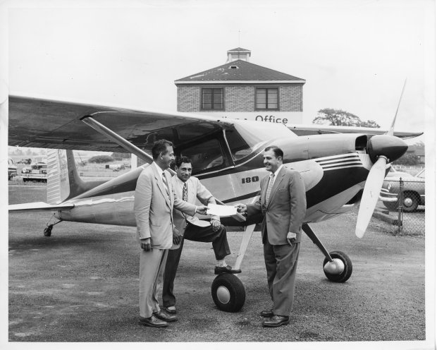 Tony Riccio and two unknown people standing next to a Cessna 180 airplane.
