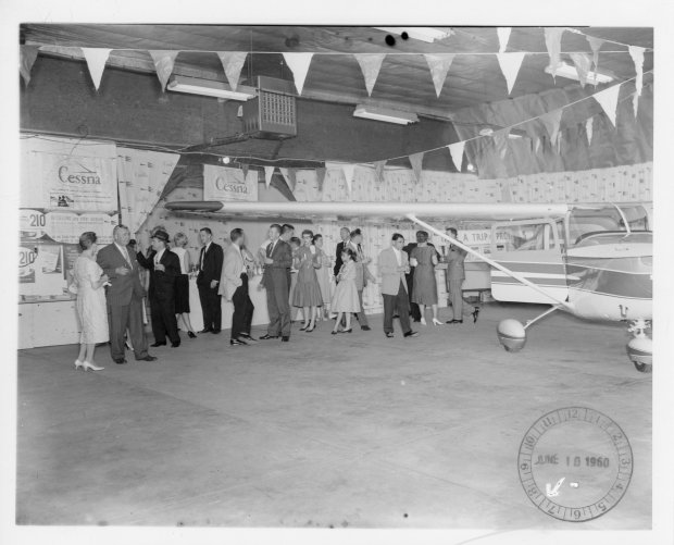 Tony Riccio and a group of unknown people gathered in the Buffalo Airpark's Quonset hangar for a Cessna marketing event on June 10, 1960.