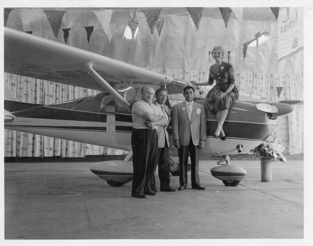 Tony Riccio and three unknown people standing next to a Cessna airplane inside the Buffalo Airpark's Quonset hangar during a Cessna marketing event.
