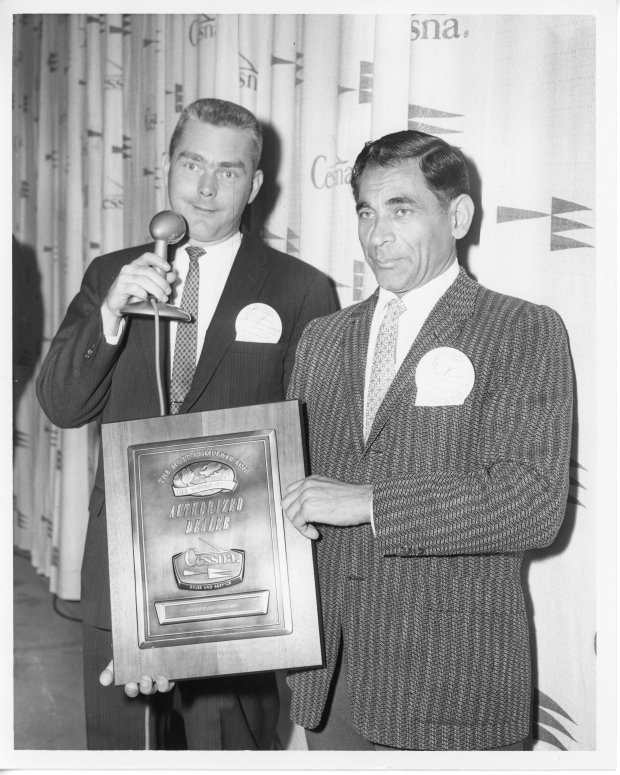 Tony Riccio holding his Authorized Dealer plaque from Cessna standing next to an unknown person.