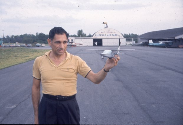 Tony Riccio standing on the Buffalo Airpark's tarmac holding a small airplane model.