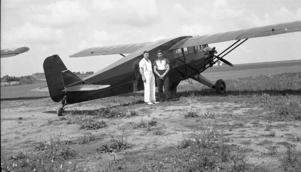 Tony Riccio and an unknown person standing along the side of Tony's Aristocrat airplane.