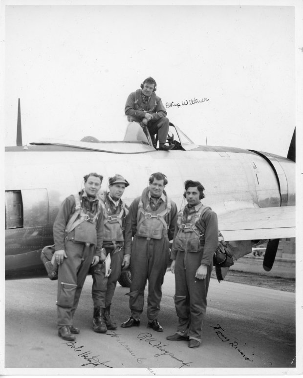 "Tony standing next to a P-47-D-25 ""Bubble Canopy"" warplane with other test pilots in his squadron."